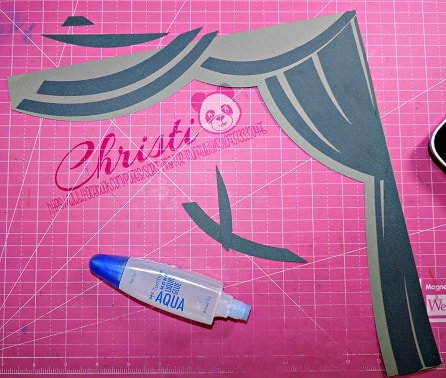 gluing the curtains on the graduation scrapbook layout